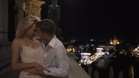 Fabelhafte Paare in der Liebe, die auf dem Balkon auf dem Hintergrund der Nachtalten Stadt küsst stock video footage