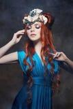 Fabelhafter Blick des Rothaarigemädchens, blaues langes Kleid, helles Make-up und große Wimpern Mysteriöse feenhafte Frau mit dem Stockbild