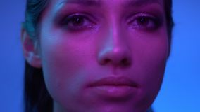 Fabelhaftes Mode-Modell in den purpurroten Neonlichtern, die sich langsam bewegen und ruhig in Kamera im Studio aufpassen stock footage