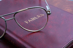 Fables. A background with an abstract view of spectacles on a very old book, with the glass focussing on the title - Fables stock photos
