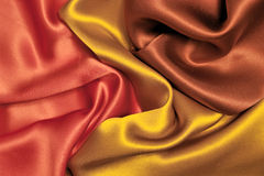 Fabric background. Elegant and soft red, yellow, brown satin background Stock Photo
