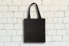 Fabric bag. Black fabric bag against vintage brick wall stock photo