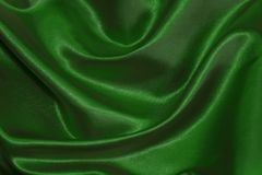Fabric beautiful folds. Background of textiles. Green color texture Royalty Free Stock Photos