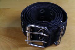 Fabric belt wind up. Black fabric belt wind up on a wooden table Royalty Free Stock Photo