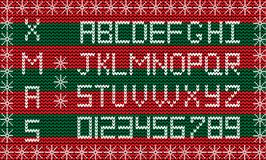 Fabric Christmas or New Year script. Knit festive winter alphabe. White knitted alphabet and numerals on red and green striped knitted fabric background framed Royalty Free Stock Photography