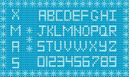 Fabric Christmas or New Year script. Knit festive winter. White knitted alphabet and numerals on blue fabric background framed with snow flakes. Fabric Royalty Free Stock Photography