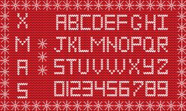Fabric Christmas or New Year script. Knitted festive alphabet. White knitted alphabet and numerals on red knitted fabric background framed with snow flakes Royalty Free Stock Photos