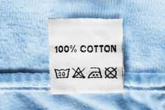 Fabric composition label. Fabric composition and washing instructions clothes label on blue cotton closeup Stock Photos