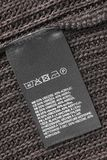 Fabric composition label. Fabric composition and washing instructions clothes label on brown knitted background Stock Photos