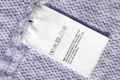 Fabric composition label. Washing instructions and fabric composition clothes label on violet knitted background Royalty Free Stock Photos