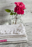 Fabric cotton kitchen towels and pink roses in a glass vase Stock Photography