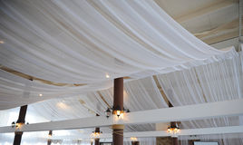 Fabric drape on the restaurant ceiling. Bright interior, lighted lantern. The decor for the wedding party. Fabric drape on the restaurant ceiling. Bright stock images