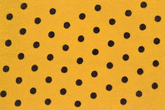 Fabric dyed in black peas on a yellow background Royalty Free Stock Photos