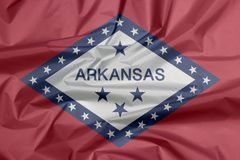 Fabric flag of Arkansas. Crease of Arkansas flag background, The states of America. stock photo