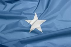 Fabric flag of Somalia. Crease of Somalian flag background. Fabric flag of Somalia. Crease of Somalian flag background, a single white five-pointed star stock illustration