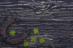 Fabric green clover leaves with horseshoe on wooden background. Royalty Free Stock Image