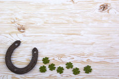 Fabric green clover leaves with horseshoe on wooden background. Royalty Free Stock Photos