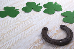 Fabric green clover leaves with horseshoe on wooden background. Stock Photography