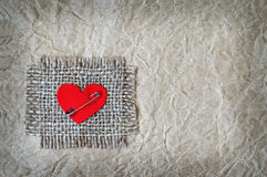 Fabric heart attached on canvas with safety pin Royalty Free Stock Photo