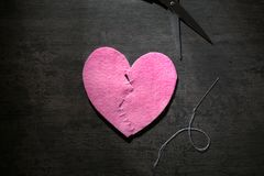 Fabric heart cut in half and sewn back together. On dark background. Relationship problems Royalty Free Stock Images
