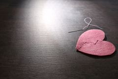 Fabric heart cut in half and sewn back together. On dark background. Relationship problems Stock Photography