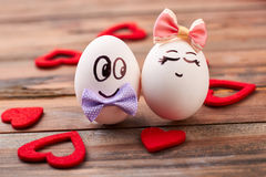 Fabric hearts near love eggs. Egg couple on wooden background. Usage of food in greeting stock photography