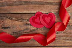 Fabric hearts and red ribbon. Curly ribbon on wooden background. Learn to surprise Stock Photos