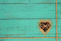 Fabric hearts with rope border on teal blue wooden background. Shabby burlap, country fabric heart and braided rope border on rustic antique teal blue wood stock image