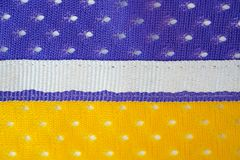 Fabric made of yellow and purple polyester background with white ribbon in the middle
