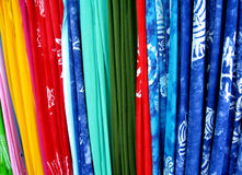 Fabric in a market. Vertical lengths of brightly colored fabric on display for sale in a market Stock Photo