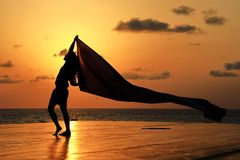 Fabric in the merry mood. Lady with windy fabric under the sunset Stock Photo