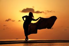 Fabric in the merry mood. Lady with windy fabric under the sunset Stock Photography