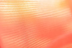 Fabric orange colored background with light penetrating through.  Stock Photography