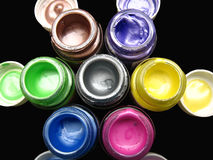 Fabric paint Background. A background of colorful fabric paint bottles,along with their respective corks Stock Images