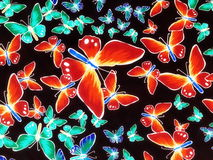 Fabric with painted butterflies. Black fabric with painted red and green butterflies Royalty Free Stock Photo