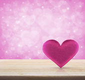 Fabric pink heart shape on wooden table over light pink heart Royalty Free Stock Image