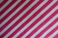 Fabric in pink and white with diagonal stripes. From above Royalty Free Stock Photo