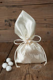 Fabric pouch wedding favor. On old wooden table stock photos