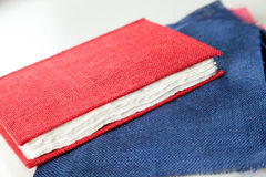 Fabric And Red Cover Book On Table In Factory Royalty Free Stock Images