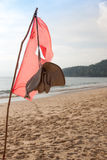 Fabric red flag at the beach. Fabric red flag and hat at the beach Stock Image