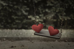 Fabric red heart on damage metal playground swing Royalty Free Stock Photo