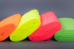 Fabric in rolls of neon colors. Tulle. neatly folded in a row. On a dark background