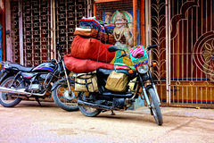 Fabric Salesman Motorbike. A fabric salesman parks his bike outside a temple in Rishikesh. His motorcycle is stacked high with his patterned cloth he is selling Royalty Free Stock Photo