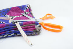 Fabric scissors and tape. New fabric colors for a beautiful tailor with scissors and a tape measure Royalty Free Stock Images
