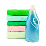 Fabric softener the bottle and a stack of towels. One bottle of blue fabric softener, stack of towels with a light shade on white background Stock Photo