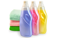 Fabric softener with a stack of towels. Three bottles of fabric softener pink, yellow and lilac, three of towels with a light shade on white background Stock Image
