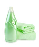 Fabric softener and towel green. Green fabric softener in the bottle and two green towels with a light shade on white background Stock Images
