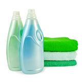 Fabric softener in two bottles and towels. Two bottles of fabric softener blue and green colors, a stack of three towel with a light shade on white background Stock Photos