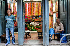 Fabric Store Sellers. Fabric store in one of the markets of Kathmandu, Nepal. 3 sellers in the entrance, each with a different stand and a different look royalty free stock image