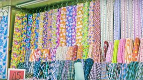 Traditional fabric store with stacks of colorful textiles, fabric rolls at market stall - textile industry background with blurred Stock Photo